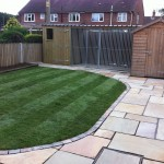 Garden with lawn and paved area with dog kennels