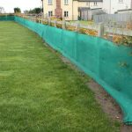 Mesh screening protective fencing in between grass and housing