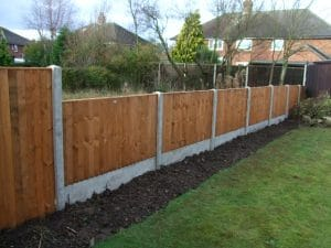 Concrete posts and wooden panel domestic fencing in garden
