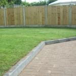 Concrete posts and wooden feather edge fencing in garden with lawn and paved path