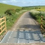 Metal cattle grid on dirt track through grassy field