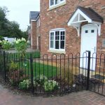 Black bow top metal railings around house