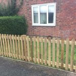 Wooden picket fencing in front of house and garden