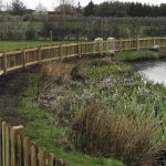 Protective picket fencing around pond
