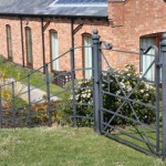 Black estate fencing gate alongside house