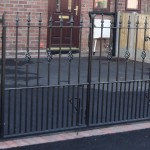 Folding metal decorative gate on driveway