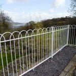 White interlaced metal railings in garden