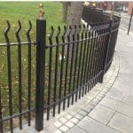 Black metal wave top fencing on footpath