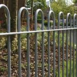 Bow top metal fencing on grass verge