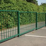 Green metal guard rail fencing on car park
