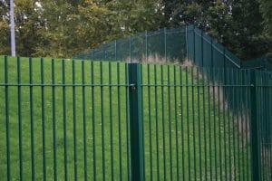 Green vertical bar metal railings around grass verge